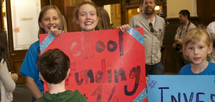 An elementary student smiles and poses with her sign
