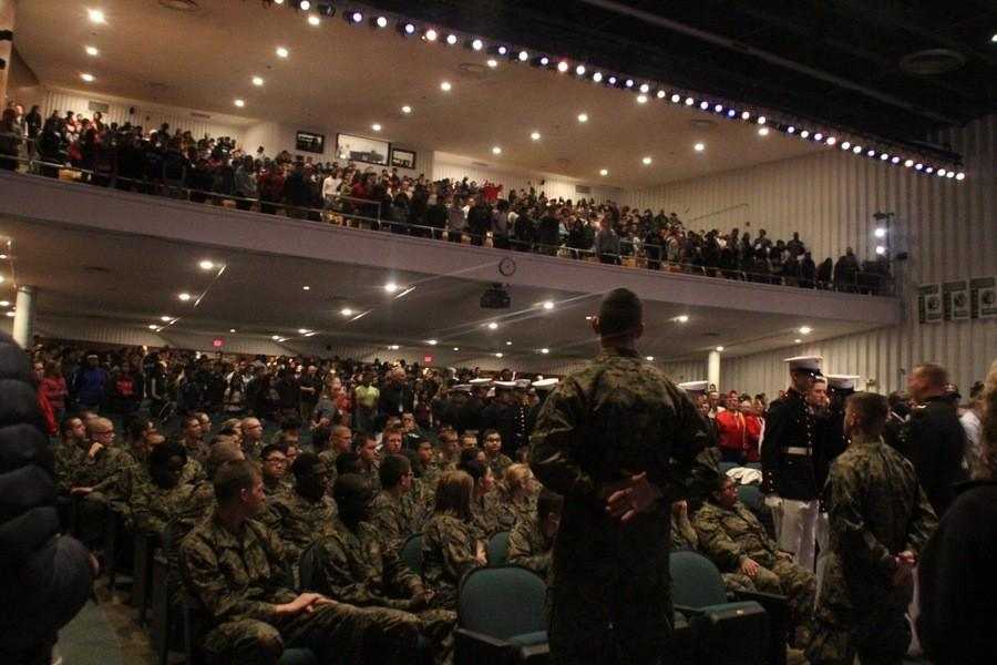 Students, staff and visitors stand as Veterans file in for the Veterans Day Assembly.