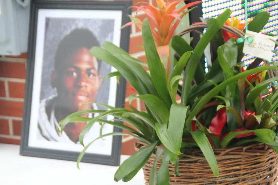 A basket of flowers is placed next to the memorial of Kendall Foster.