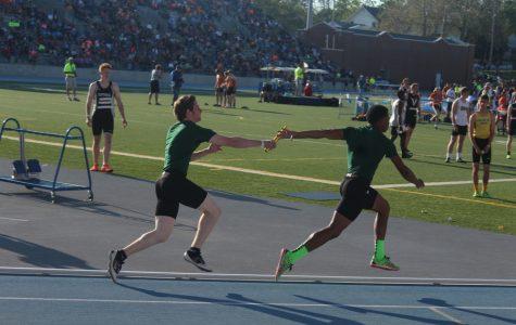 Junior Andrew Phillips hands the baton off to Sophomore Elijah Facey.