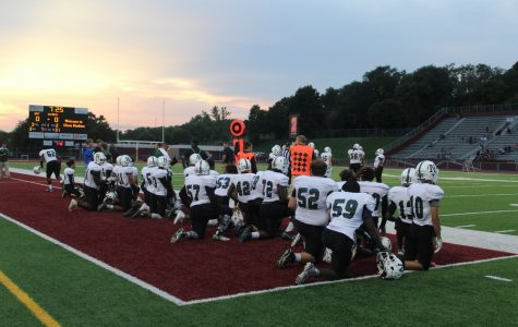 The team takes a knee for injured senior Jesse Malavong.