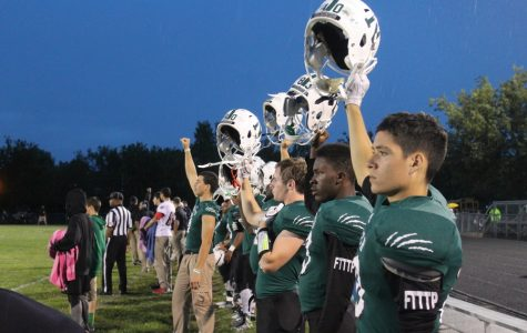 The team lifts their helmets for kickoff.