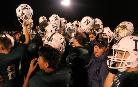 The team holds up their helmets after the big win Friday, August 26, 2016 against Waterloo East Trojans.