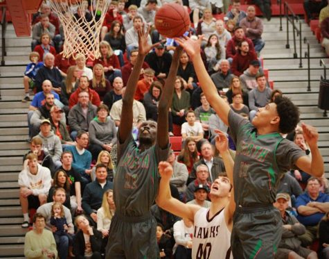 Senior, Jal Bijiek and Junior, Jaihon McCaleb jump up for a rebound after an Ankeny Hawk misses the free throw.