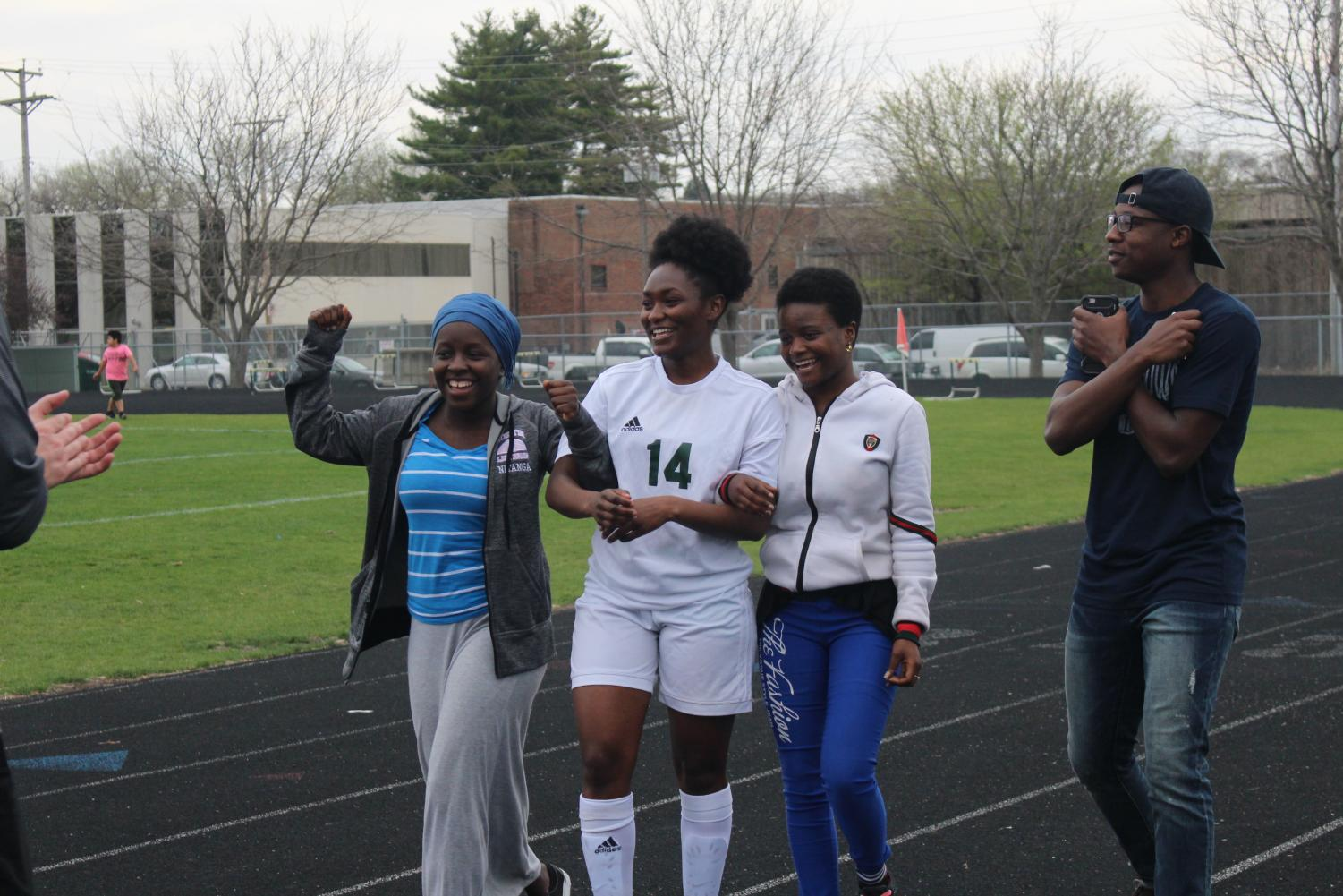 Senior Tuyishime Florance walking with friends towards her coach and teammates.